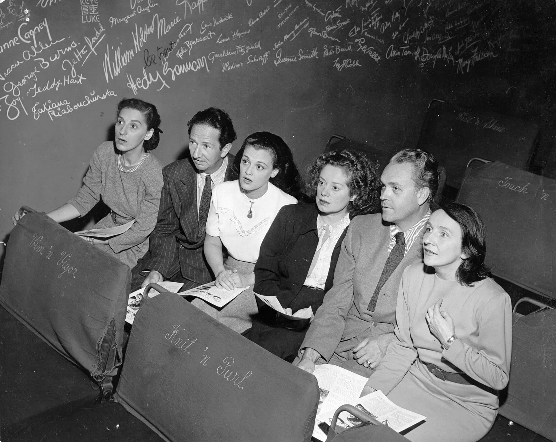 Dorothy Neumann, Harry Burnett, Frances Osborne, Elsa Lanchester, Forman Brown, and Lotte Gosler sit in the Turnabout Theater, with the autograph wall in the background.