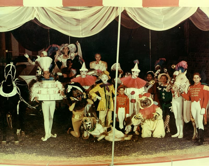 "Cast of ""Tommy Turnabout's Circus,"" A few horses and aproximatly 15 casts members in costume pose under a circus tent"