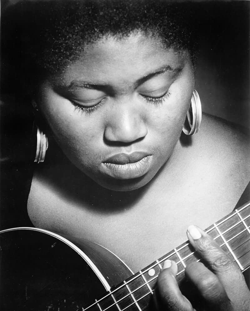 Portrait of Odetta playing guitar