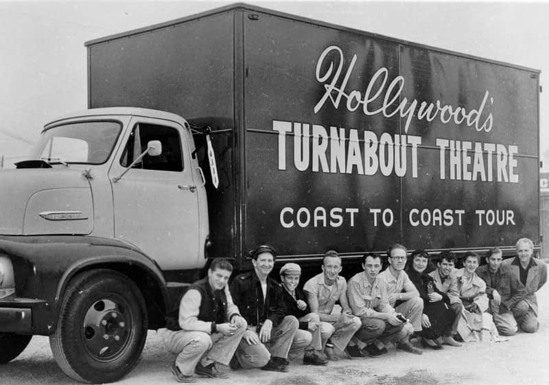 Cast and crew oof Thruabout Theater pose for a photo along the side of their large show truck