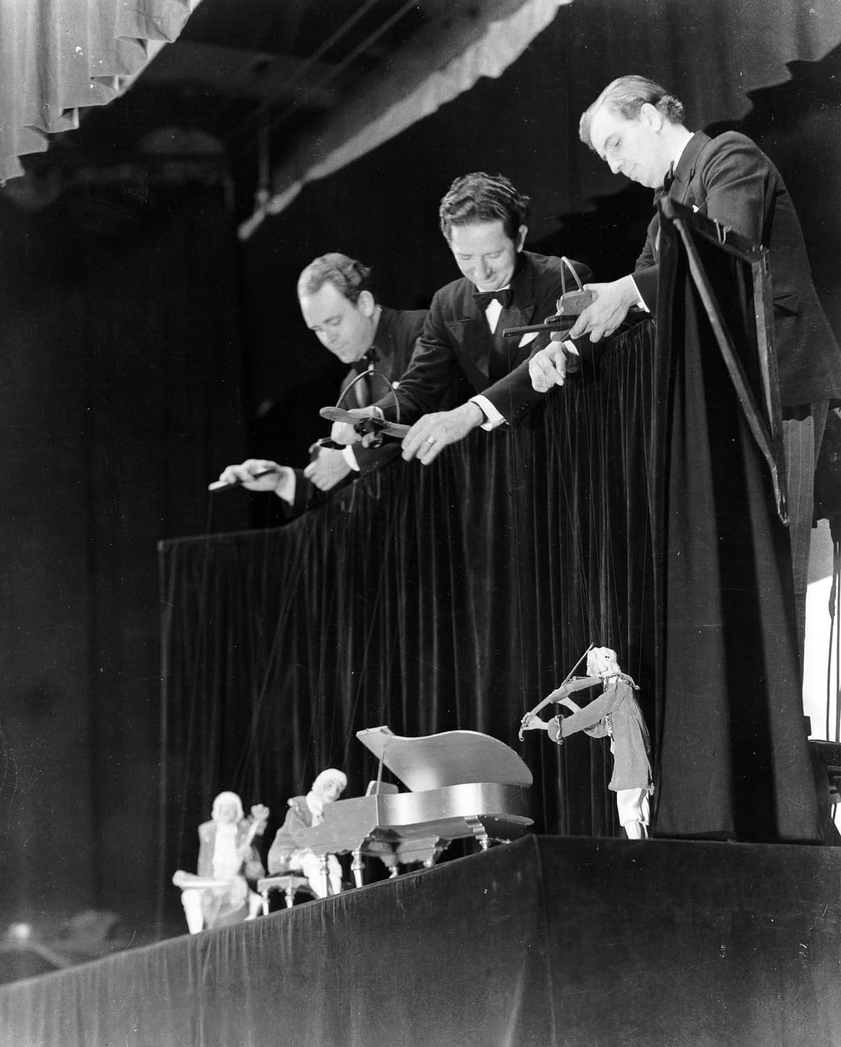 wearing tuxedos, the Yale Puppeteers hang the Haydn Trio puppets over a black curtain at the Barbizon Plaza