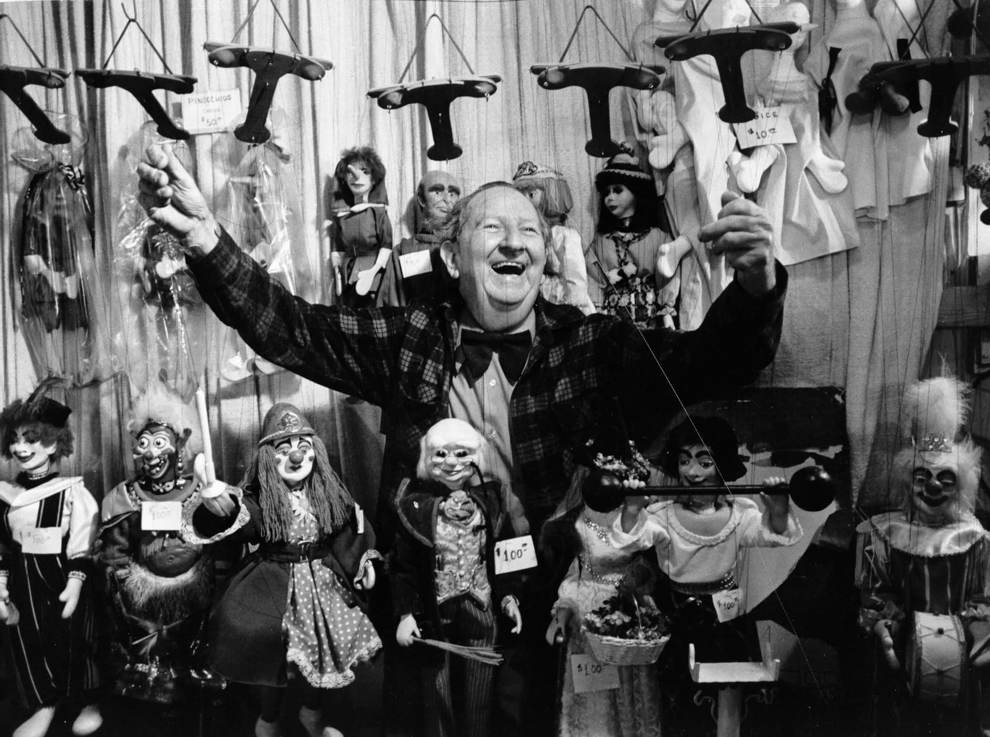 A Smiling Harry Burnett poses with arms extended surrounded by Puppets